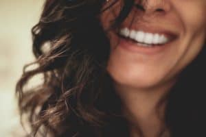 Women is showing off her smile. This is an example of healthy looking teeth.