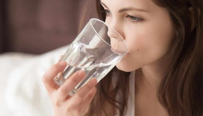 Young dehydrated woman feeling thirsty, drinking mineral water from glass